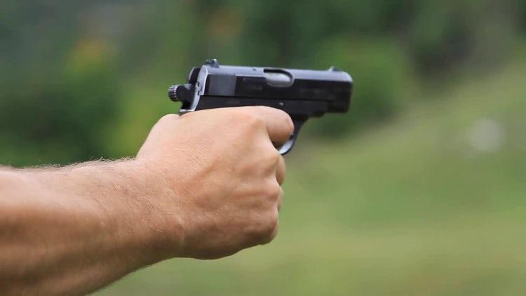Man Fires A Gun Outdoors: Stock Video
