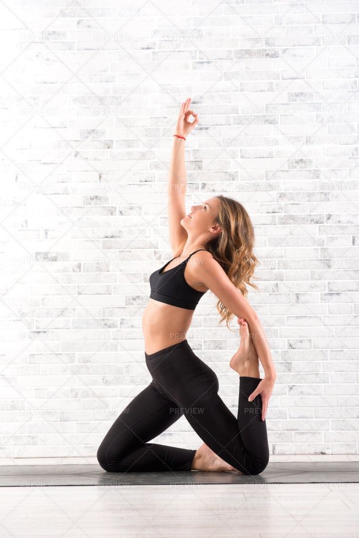 Woman Doing Ardha Dhanhrasana Yoga Pose: Stock Photos