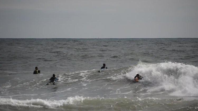 Surfers Swimming Into Sea: Stock Video