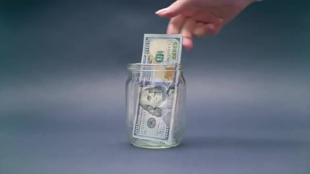 Saving US Dollars In Glass Jar: Stock Video