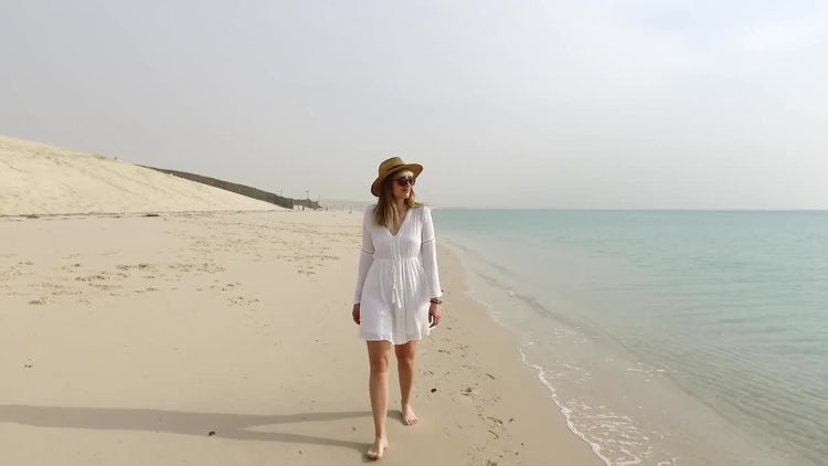 Woman Walking Down A Beach: Stock Video