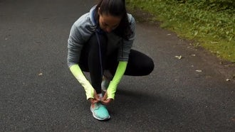 Woman Runner Tying Shoelaces: Stock Video