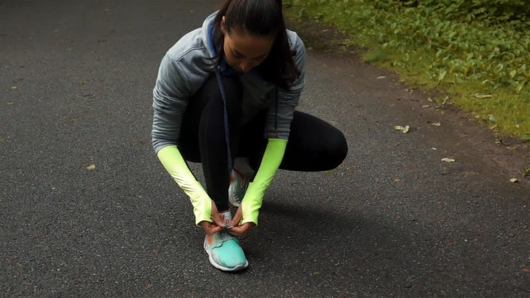 Woman Runner Tying Shoelaces: Stock Video