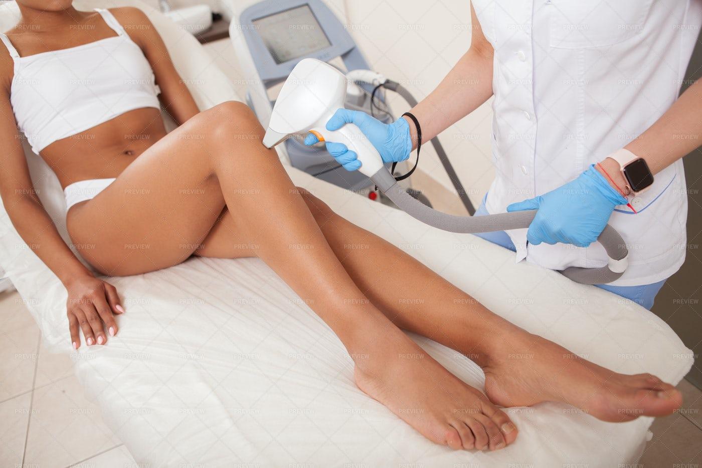 Cosmetician Using Laser Hair Remover: Stock Photos