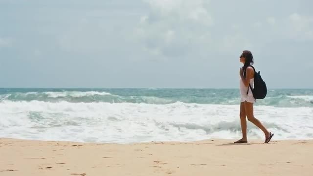 Woman With A Backpack Walking On Beach: Stock Video