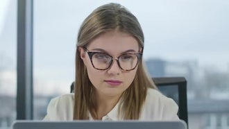 Young Lady With Glasses Looking At The Laptop: Stock Video