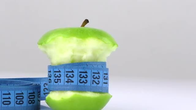 Measuring Tape Around Bitten Apple: Stock Video