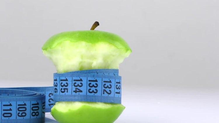 Measuring Tape Around Bitten Apple: Stock Video