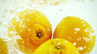 Four Oranges Dropped Into Water: Stock Video