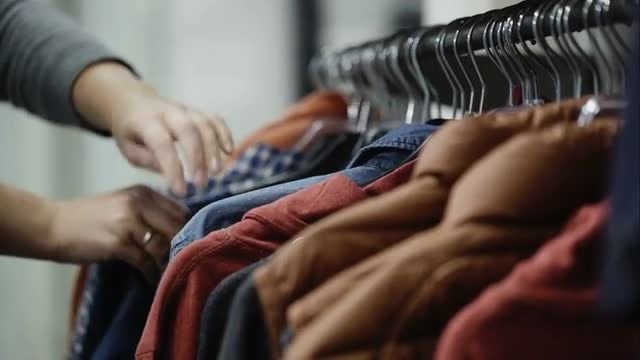 Woman Looks Through Jackets and Shirts: Stock Video