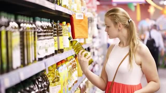Young Woman Buying Olive Oil: Stock Video