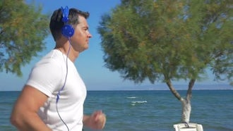 Man Jogging Seaside With Music: Stock Video