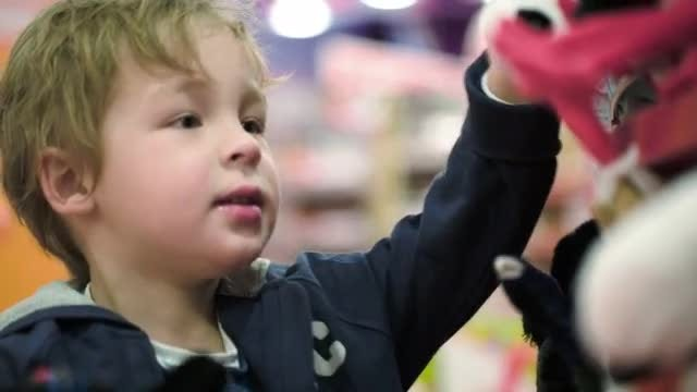 Little Child Choosing Soft Toys: Stock Video