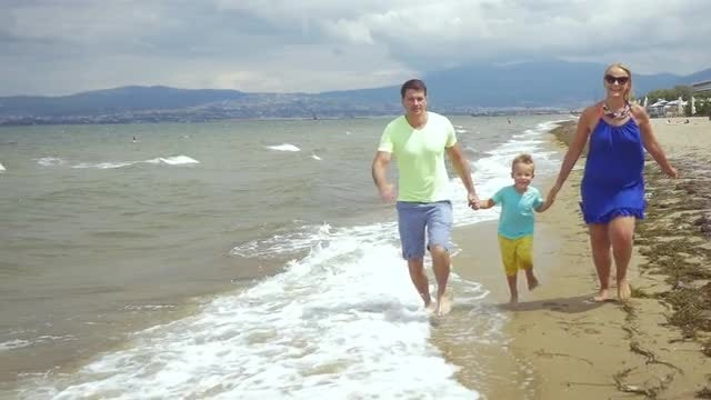 Happy Family Running On The Seaside: Stock Video