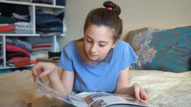 Young Girl Browsing A Book: Stock Video