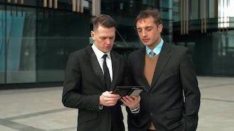 Businessmen Discussing With A Tablet: Stock Video