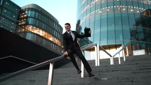 Businessman Sliding Down Stair Rail: Stock Video