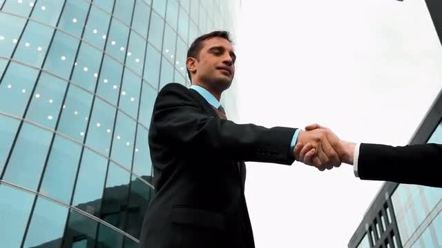 Businessmen Exchange A Firm Handshake: Stock Video