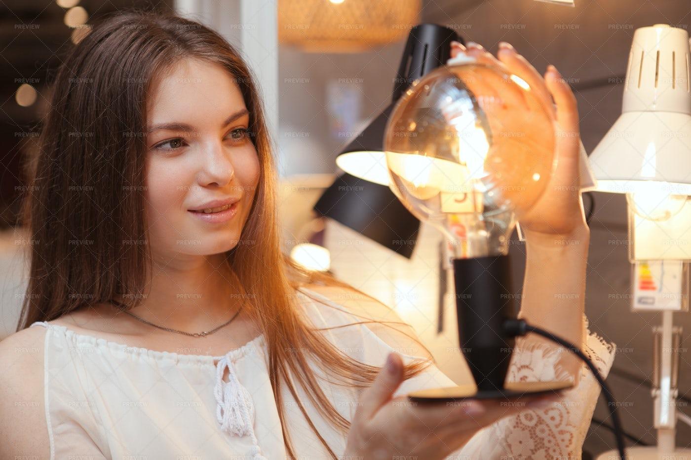 Woman Choosing Lamp: Stock Photos