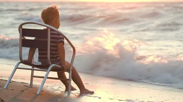 Boy Sitting By The Sea: Stock Video