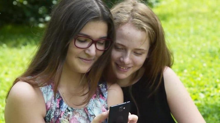 Teenage Girls Using Smartphone Outdoors: Stock Video