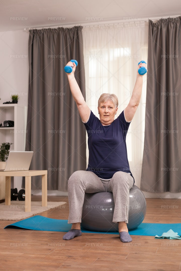 Elderly Woman Holding Dumbbells: Stock Photos