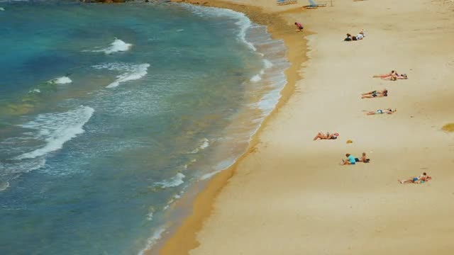 Beachgoers Relaxing On The Beach: Stock Video
