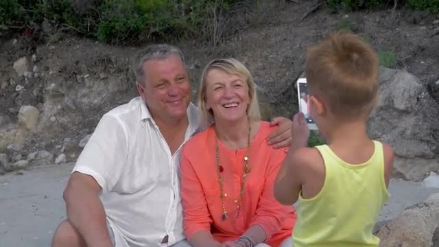 Boy Taking Photos Of Grandparents: Stock Video