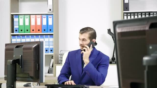 Businessman Talks On Office Phone: Stock Video
