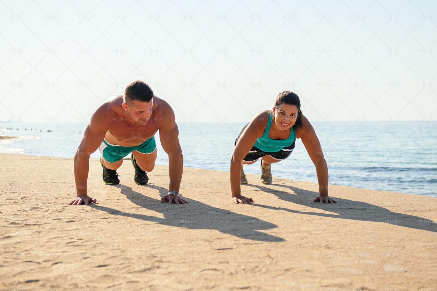 Man And Woman Do Push-Ups At The Beach: Stock Photos