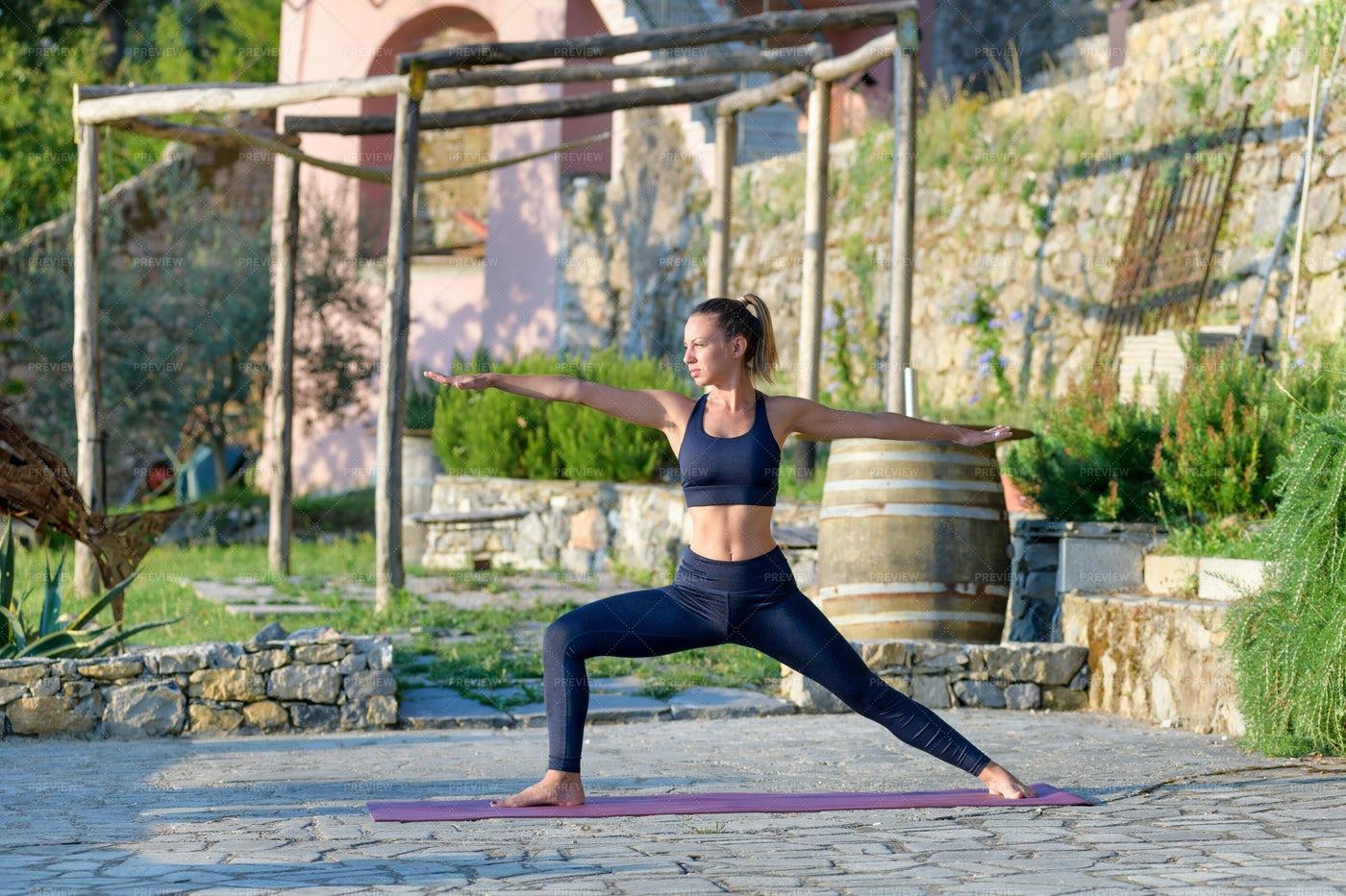 Woman In A Warrior Yoga Pose: Stock Photos