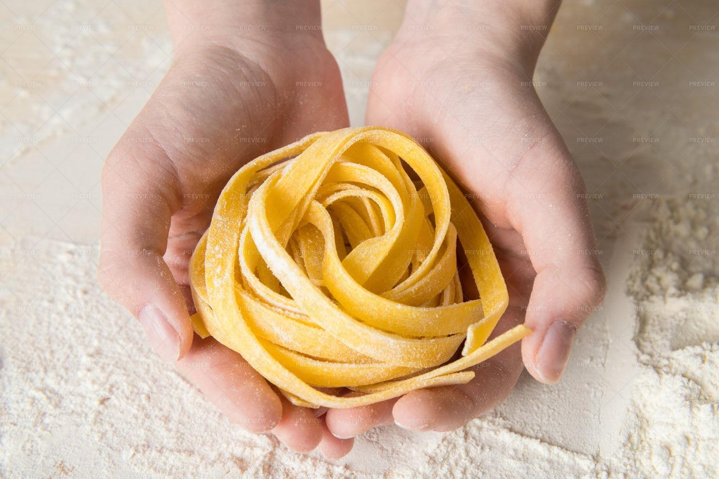 Hands Holding Tagliattelli Pasta: Stock Photos