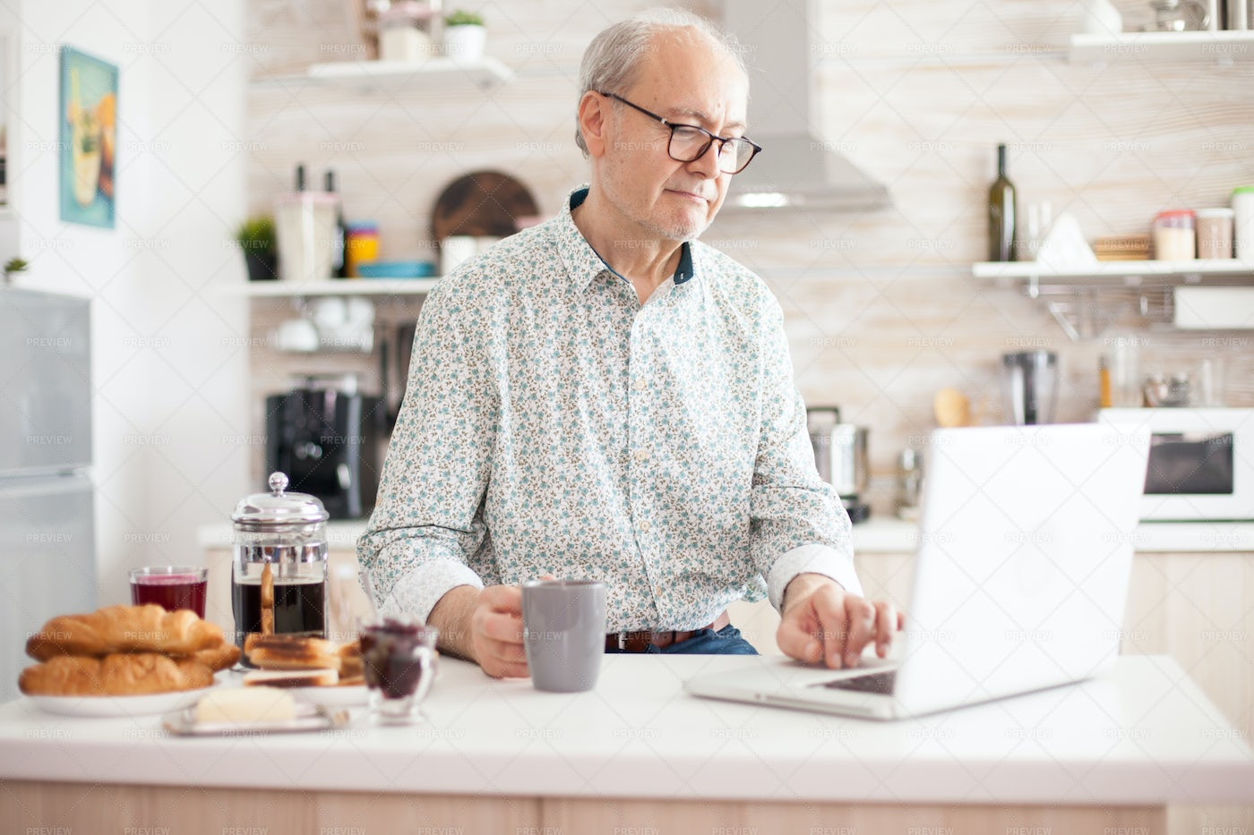 Grandfather Using Laptop In The Kitchen: Stock Photos