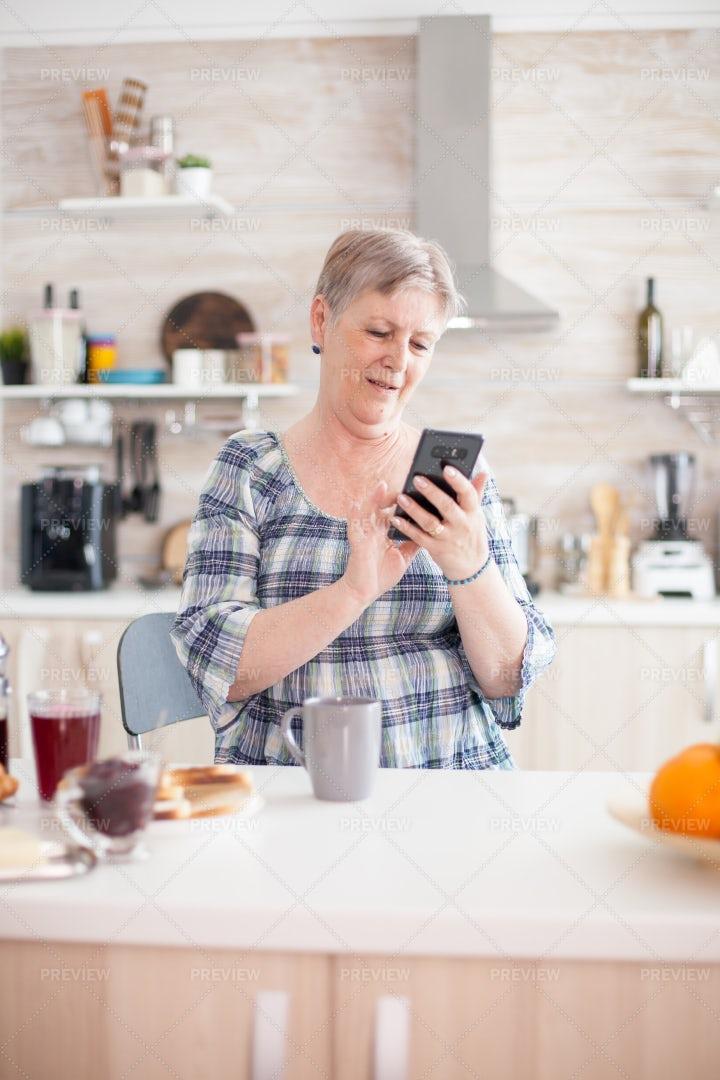 Elderly Woman Texts Family At Breakfast: Stock Photos