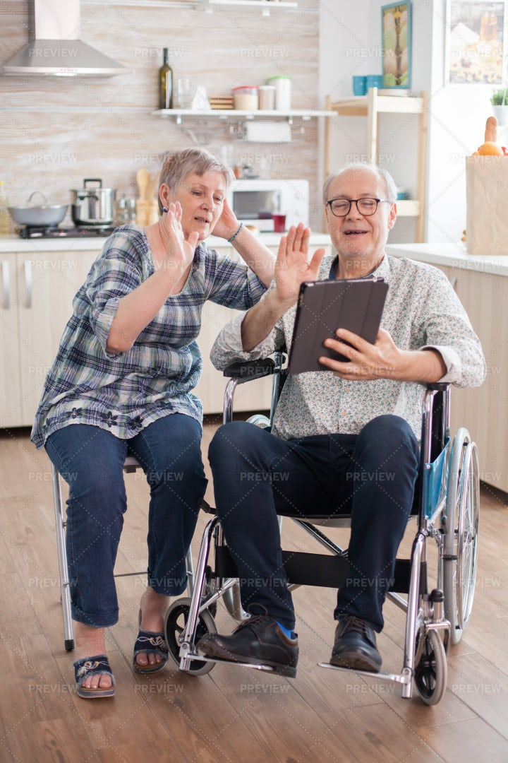 Retired Couple Waving On Video Call: Stock Photos