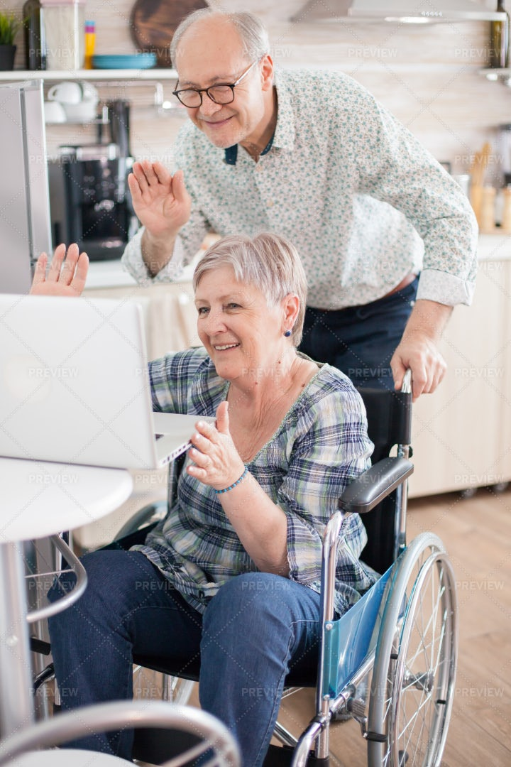 Seniors Waving During Video Call: Stock Photos