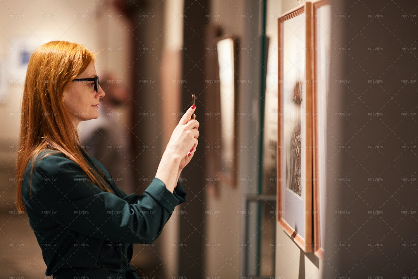 Woman Taking Photo Of Painting: Stock Photos