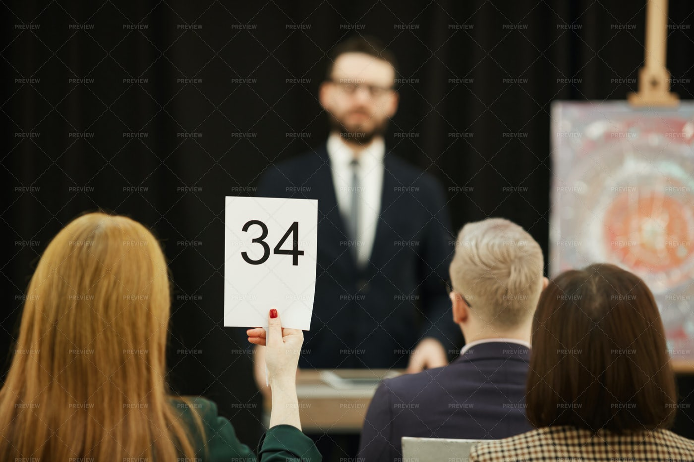 Woman Sitting At An Auction: Stock Photos