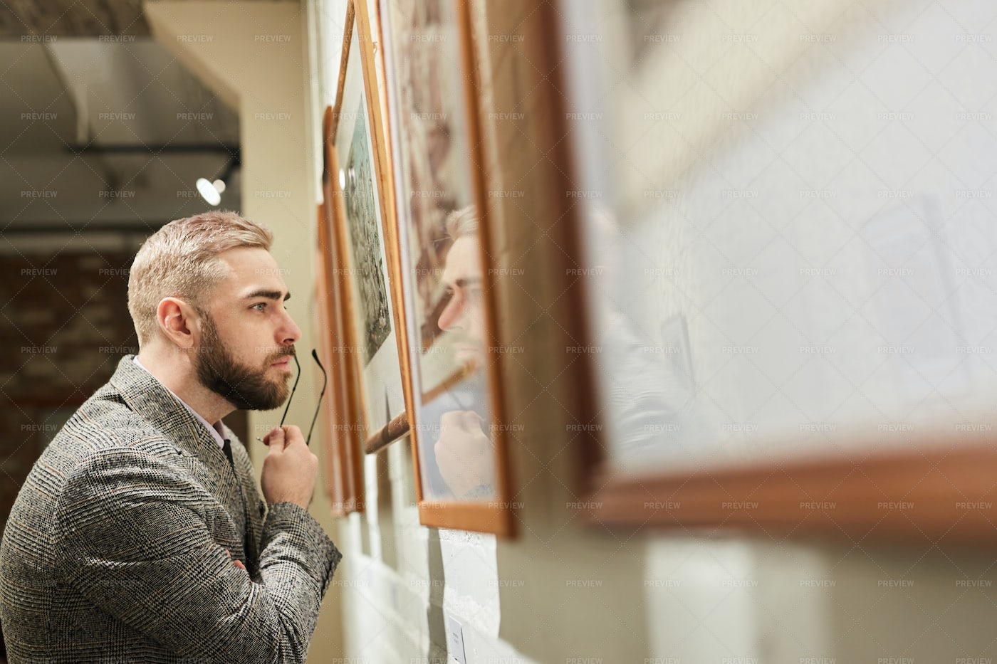 Man Examining The Paintings: Stock Photos