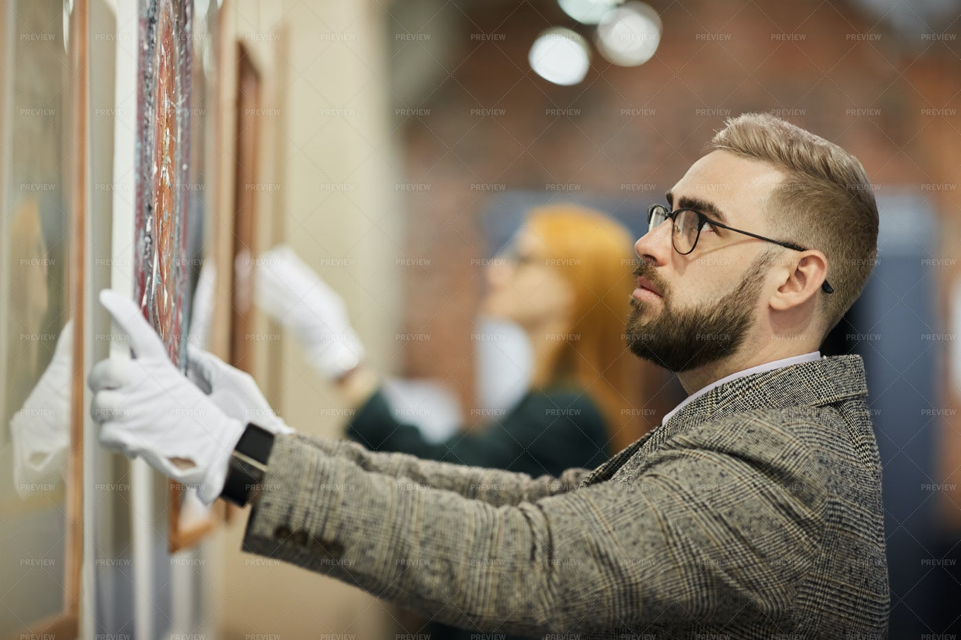 Art Manager Hanging The Painting: Stock Photos