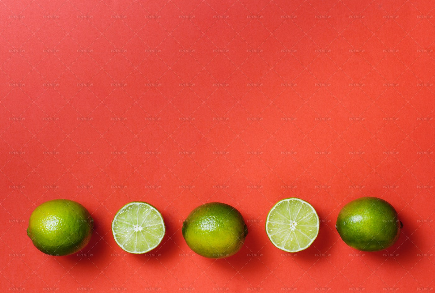 Row Of Limes On Red: Stock Photos