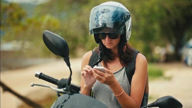 Female Biker Using Her Smartphone: Stock Video