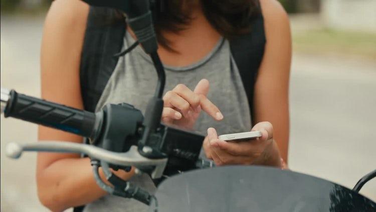 Female Biker Scrolling On Smartphone: Stock Video