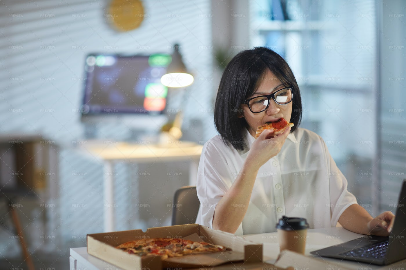 Eating As She Works: Stock Photos