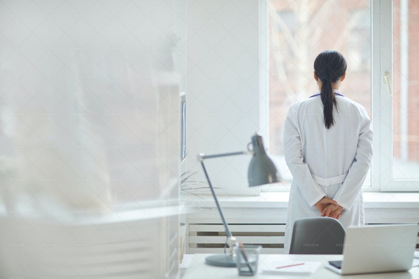 Female Doctor Looking Out Window: Stock Photos