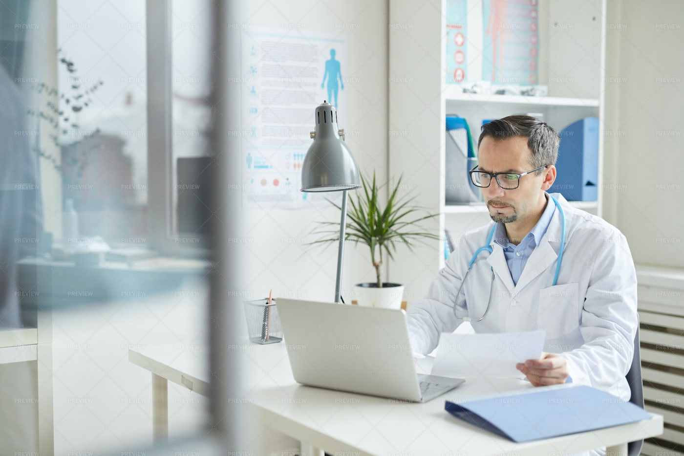 Doctor Working On Laptop In Office: Stock Photos