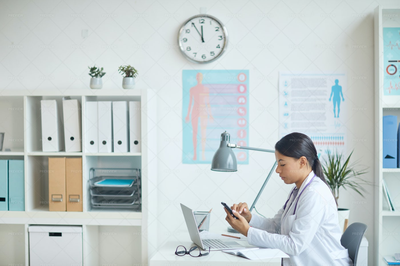 Pediatrician Using Phone In Her Office: Stock Photos