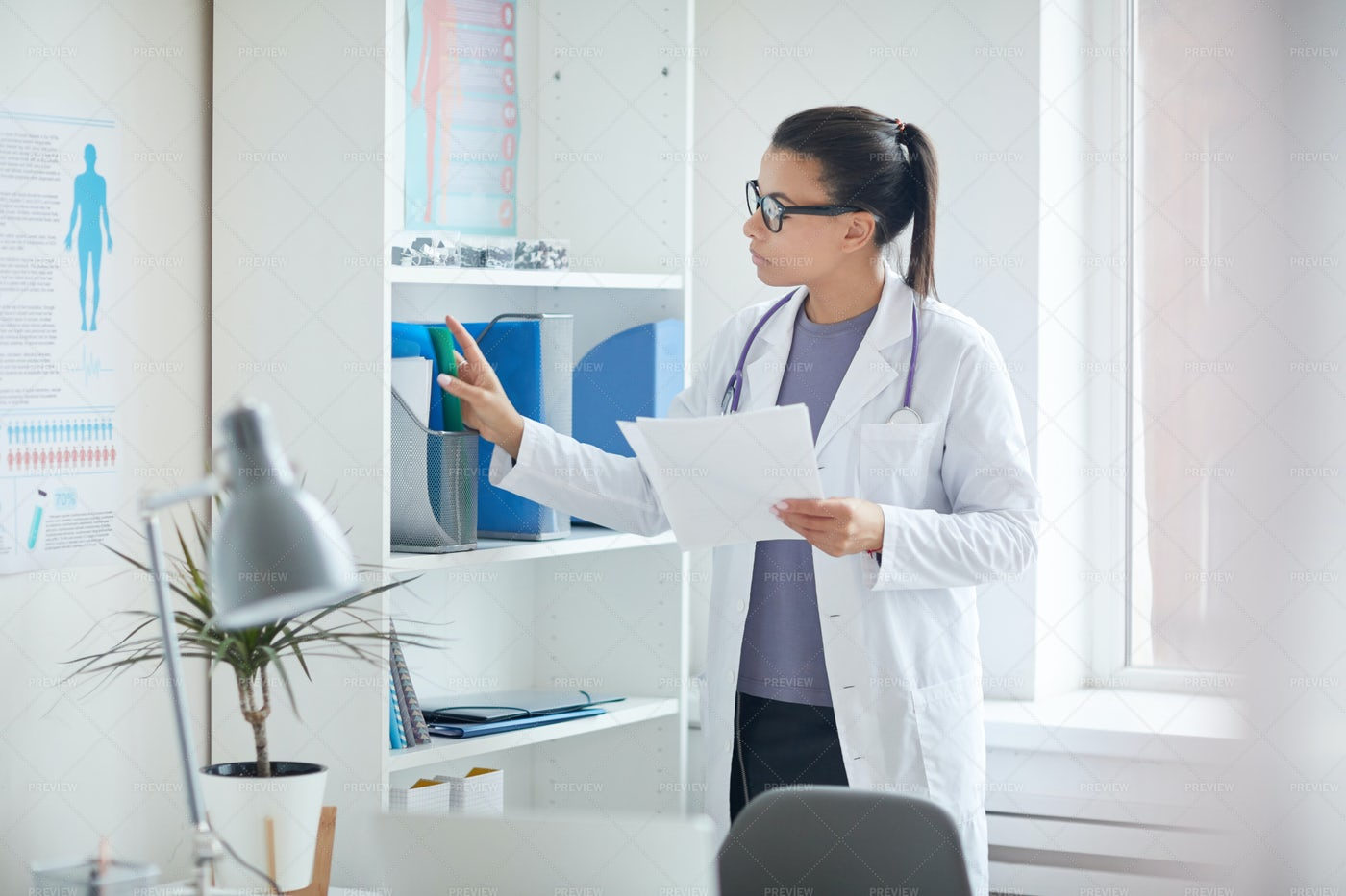 Female Doctor Filing Documents: Stock Photos