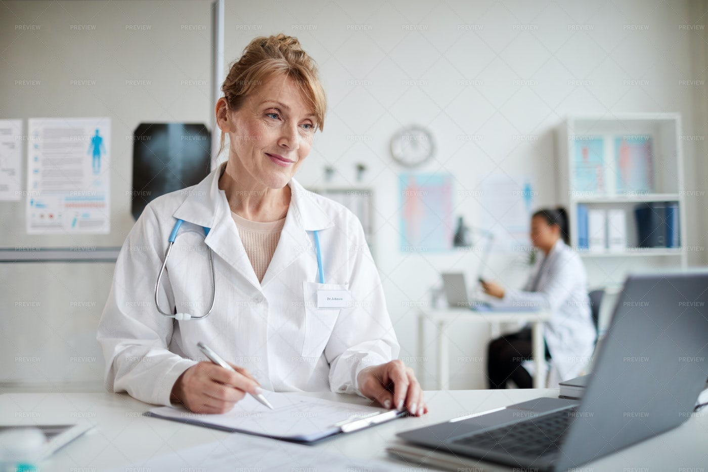 Female Doctor Taking Notes: Stock Photos