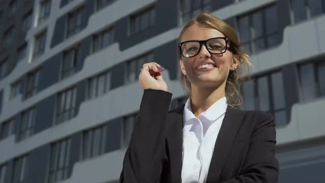 Businesswoman in Smart Suit Putting on Glasses: Stock Video